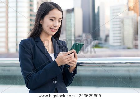 Business woman using mobile phone in the city