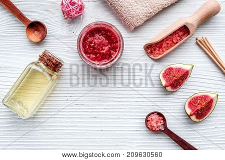 organic cosmetic set with fresh fig, bath salt, oil and scrub on white wooden table background flat lay mock-up