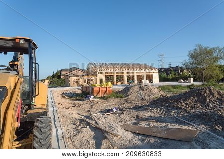 Wood frame house under construction with foundation in Humble Texas USA. New stick built framing one floor commercial building. Excavator industrial dumpster and pile of beams logs sand gravel