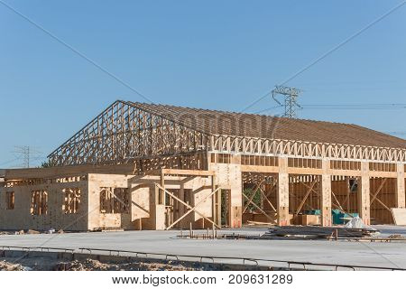 Wood frame house under construction with foundation in Humble Texas USA. New stick built framing one floor commercial building clear blue sky. Pile of beams log sand gravel. Industrial background