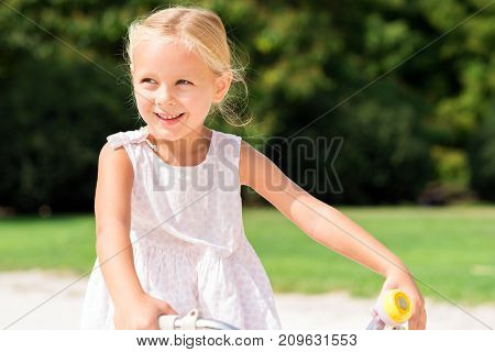 Smiling beautiful child riding on her bike