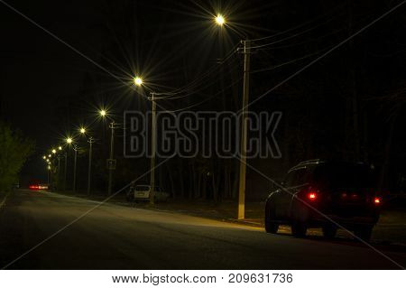 The car is lit by night street lamps