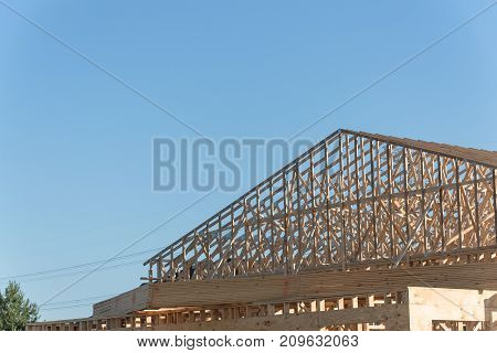 Close-up roof wood frame house under construction with foundation in Humble Texas USA. New stick built framing one floor commercial building. Pile of beams log sand gravel. Industrial background