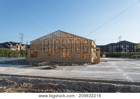 Wood frame house under construction with foundation in Humble Texas USA. New stick built framing one floor commercial building near apartment complex blue sky. Pile of beams logs sand gravel