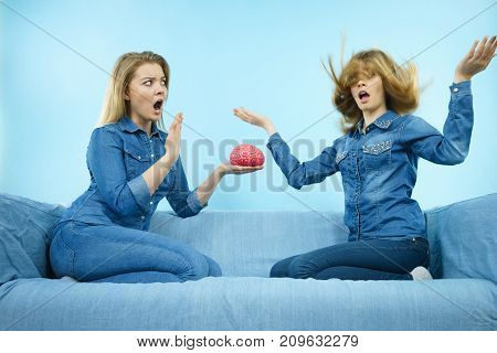 Friendship human relations concept. Two women friends or sisters wearing jeans shirts thinking about solving problem holding fake brain.