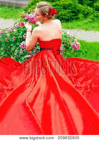 Woman in long red dress poses near flowers in garden, back view