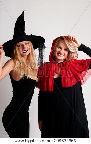Beautiful girls in halloween costume witch and little red riding hood on white background