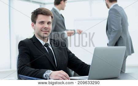 successful businessman sitting at the table with an open laptop