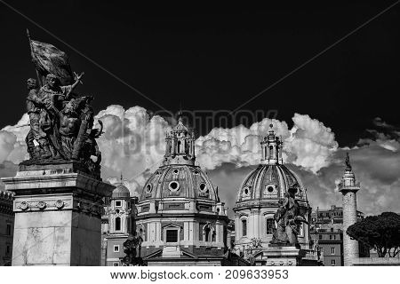 Twin Churches beautiful domes with ancient Trajan Column and clouds seen from Altar of Nation Monument in the center of Rome (Black and White)