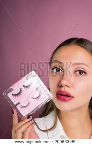 A beautiful girl with big eyes holds false eyelashes in her hands. Face close-up, isolated on a pink background