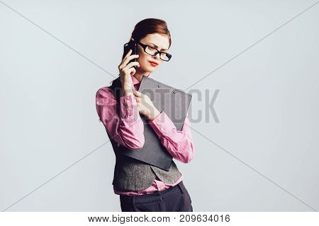 girl in glasses and with red lips holds a folder with papers in her hands and talks on the phone, isolated