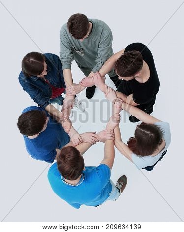 Top view of young people with their hands together in a circle.