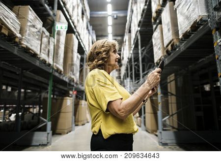 A Caucasian woman is checking stock inventory