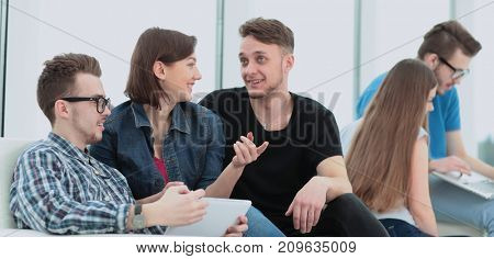 couple of University students sitting on a sofa with friends in