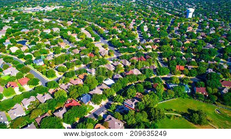 aerial view above Suburb Neighborhood complex growing modern living areas outside of austin texas growing suburbia suburban community green landscape thousands of homes