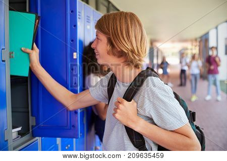 White teenage schoolboy using locker in school corridor