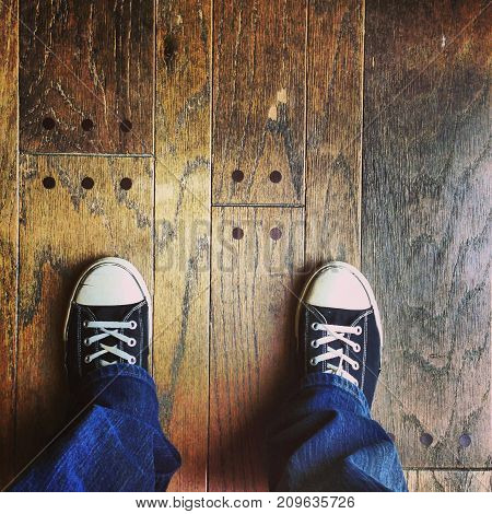 a person wearing sneakers standing on wood floor.