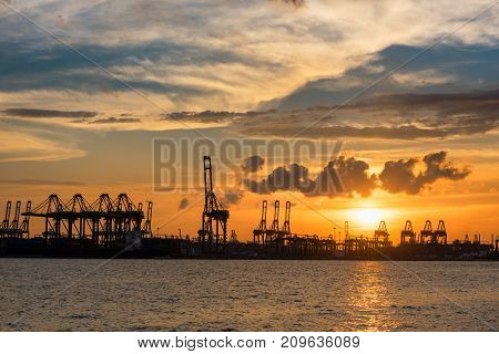 Silhouette sunset scene in Singapore shipping yard. Cargo and terminal of shipping.