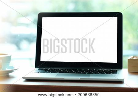 Laptop notebook computer with blank screen on wood table by window background mock up display business and technology online education technology lifestyle concept