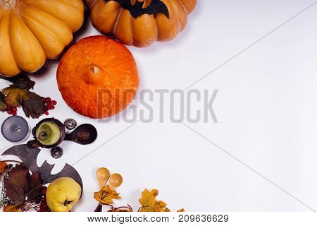 composition for decorating a house for halloween, on a white table lie yellow and orange pumpkins, burning scented candles, yellow leaves and wooden spoons