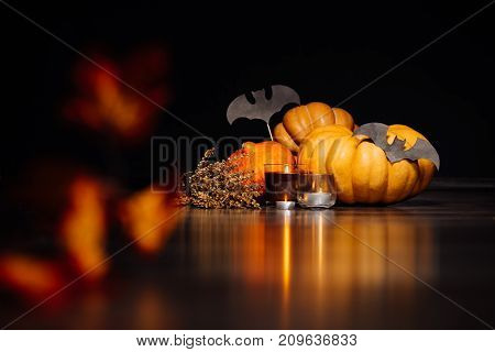 composition for decorating the house for halloween lie yellow and orange pumpkins, burning scented candles