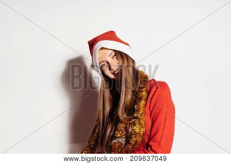 young happy girl celebrating Christmas and New Year in fashionable sweater and golden tinsel
