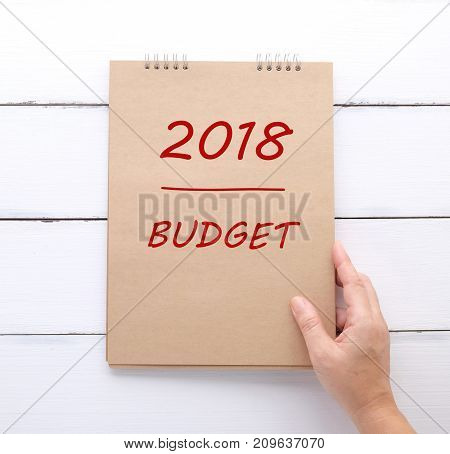 Hand holding recycle paper notebook with 2018 budget over white wood background sucess in business concept