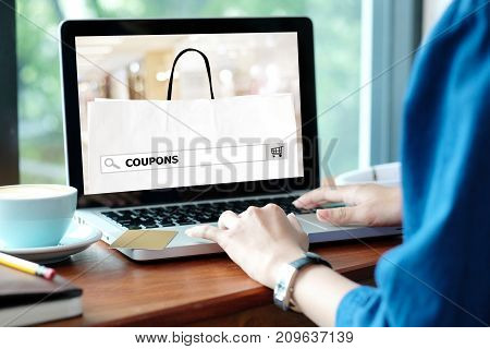 Woman hands typing laptop computer with coupon word on search bar over blur store on screen digital marketing business and technologyscreen business andtechnology concept shopping online digital marketing