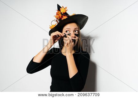 Beautiful young woman in witches hat and costume.. Wide Halloween party art design