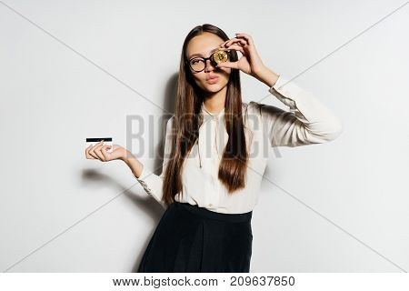 young successful modern business lady holding a gold bitcoin and a bank card