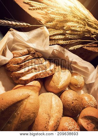 Homemade bakery concept : fresh bread and wheat on the wooden table with warm light