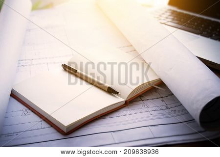 architect workplace background : notebook on blueprints for architectural plan with laptop on table in architect man working office Vintage light effect.