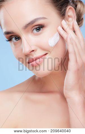 Young Beautiful Woman Applying Cream
