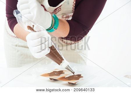 A close-up of a woman a confectioner in a white apron pours hot milk chocolate through a pastry syringe over tortoise-shaped molds. Preparation of chocolate sweets