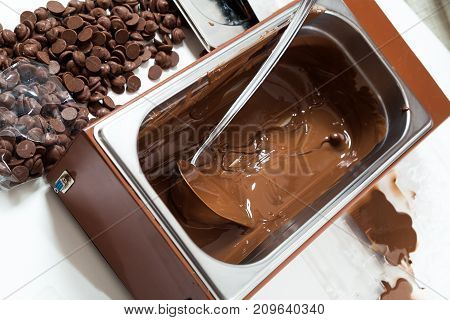 A close-up of a large mettalic container with liquid hot chocolate next to it are small pieces of solid Belgian chocolate