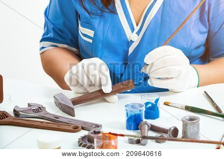 Close-up of a woman a confectioner in blue uniform and white disposable gloves paints a hammer from milk chocolate with an edible paint brush not a white table there are other edible tools