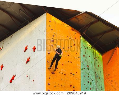The young woman on rock wall in sport center outdoor