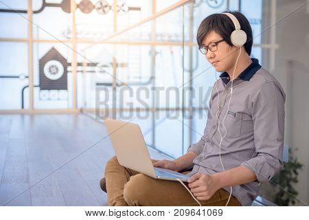 Young Asian man dressed in casual style using laptop computer while listening to music. Digital nomad working in co working space modern IT lifestyle with work life balance concept.