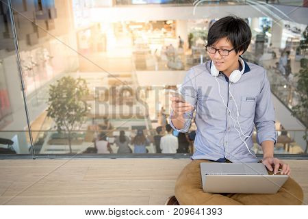 Young Asian man dressed in casual style using smartphone and laptop. Digital nomad working in co working space modern IT lifestyle with work life balance concept.
