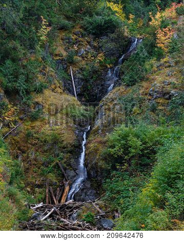 Natural garden with a waterfall passing through a colorful Autumn scene.