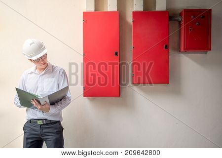 Young Asian Electrical Engineer holding files while wearing a personal protective equipment safety helmet at construction site with red electric control panel. Engineering Maintenance concept.