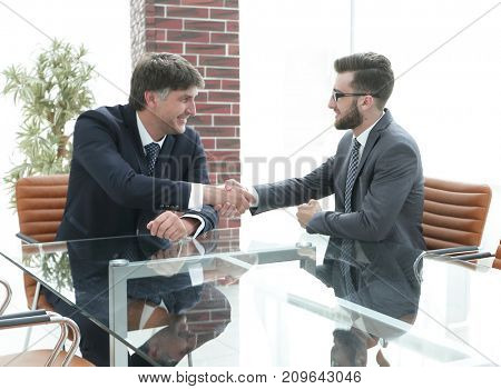 Business partners shake hands after discussing the contract