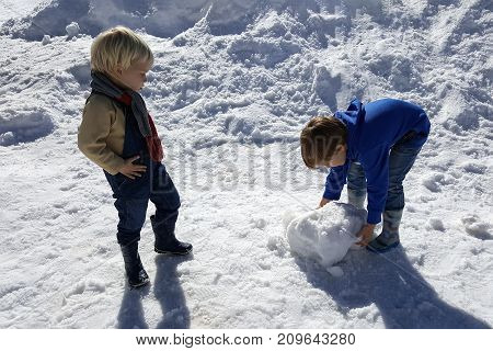 Two boys play in the winter on snow. 3 years child hands in pants is looking on 6 years kid bends down is working, trying to lift.