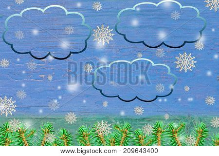 Christmas and new year background. Pattern of white plastic snowflakes close up with branches of blue spruce on a blue and green natural wood background c clouds for text insertion