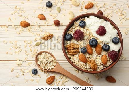 Healthy Breakfast. Oatmeal, Blueberries, Raspberries And Nuts On White Wooden Table. Top View With C