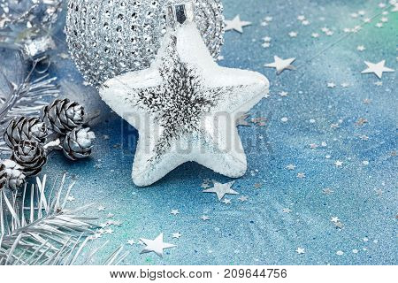 Silver Christmas Decorations And Fir Cones On Blue Background