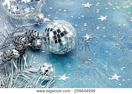 Silver Balls And Fir-tree Branches With Star Confetti On Festive Background