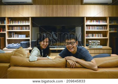 Happy Couple Watching A Movie In Living Room At Night