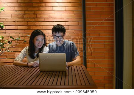 Happy Asian Couple Are Working Together At Night