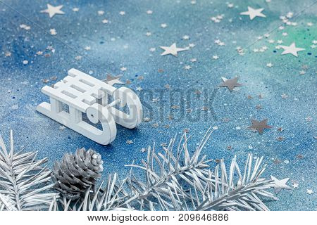 White Sledge And Silver Christmas Tree Branches With Cone On Blue Background